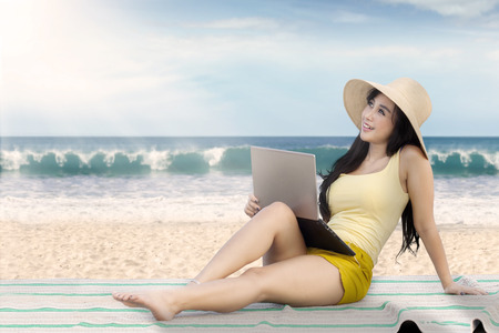 beach mat: Portrait of beautiful girl sitting on the mat while using a laptop at the beach Stock Photo