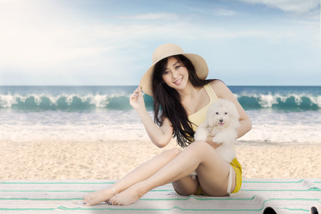 beach mat: Young woman wearing hat and holding her puppy while sitting on the mat at beach Stock Photo