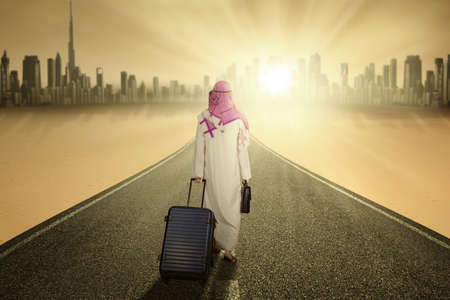 arab: Image of Arabic businessman walking on the road while carrying luggage and wearing islamic clothes