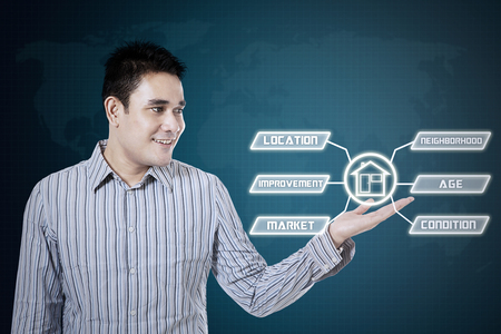 japanese people: Asian man smiling and showing house icon on the virtual screen Stock Photo