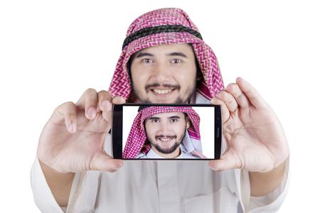 thobe: Portrait of Arabian man using a smartphone to take selfie photo in the studio