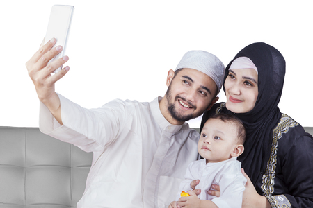 family isolated: Happy Arabic family using a mobile phone to take selfie picture together while sitting on the sofa Stock Photo
