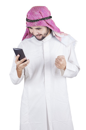 Picture of Arabic businessman reads message on his mobile phone while expressing his success Stock Photo
