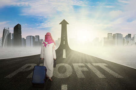 return trip: Picture of Arabian businessman walking on the road while carrying bag with a profit word on the road Stock Photo