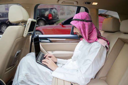 riches adult: Portrait of Arabic young businessman working in the car with a laptop computer