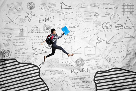 Picture of female student jumping through a gap on the crumpled paper background