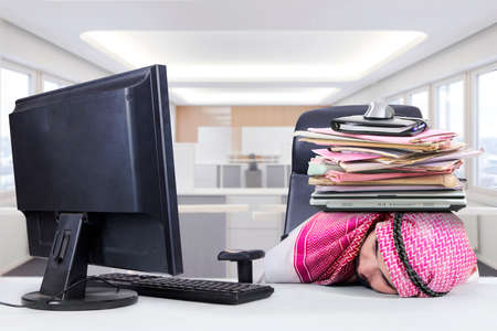 thobe: Picture of middle eastern worker wearing traditional clothes and sleeping in the office with a pile of paperwork on his head Stock Photo