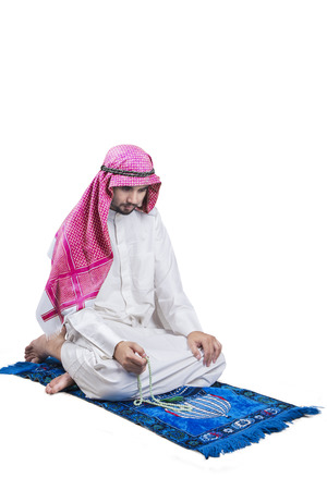 worshipper: Portrait of a young Arabic person sitting on the carpet while dhikr and wearing traditional clothes