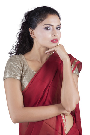 indian saree: Pretty Indian female model looking at the camera while posing and wearing a red saree clothes in the studio