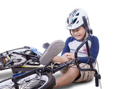 crash helmet: Wounded child falling from his bike and crying while holding his knee, isolated on white background