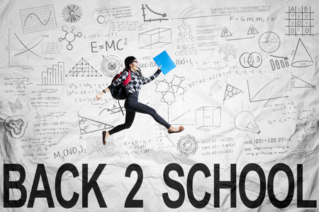 high spirits: High school student back to school and jumping on the crumpled paper background with scribbles