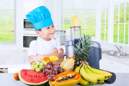 licuadora: Retrato de un niño pequeño que llevaba un sombrero de cocina mientras hace el zumo de frutas en la cocina en el hogar