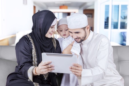 tablet computer: Picture of happy muslim family wearing islamic clothes and sitting on the sofa while using a digital tablet, shot at home