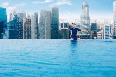 arena: Retrato de niño alegre disfrutar de la libertad mientras está sentado en el lado de la piscina en la azotea de un rascacielos