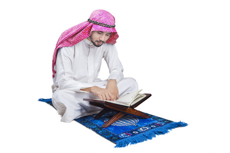 koran: Portrait of Arabic person sitting on the carpet while reading Quran in the studio, isolated on white background Stock Photo