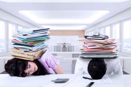 work stress: Portrait of two exhausted businesspeople sleeping in the office with a pile of paperwork on their head Stock Photo