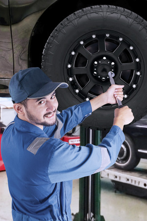 replace: Portrait of Arabic mechanic working in the workshop and replace a car wheel