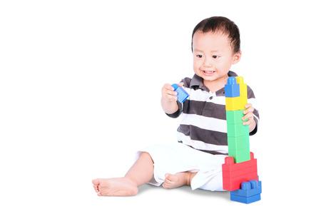bebe sentado: Retrato de un niño masculino lindo que se sienta en el estudio mientras juega con los juguetes, aislado en fondo blanco Foto de archivo