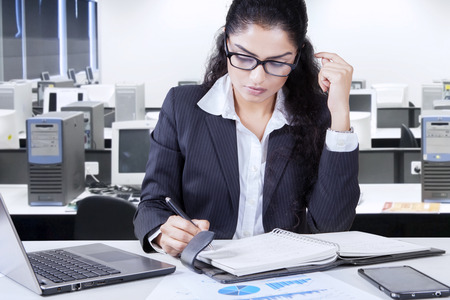 note notebook: Portrait of pretty businesswoman working in the office and looks busy while making a note on the notebook