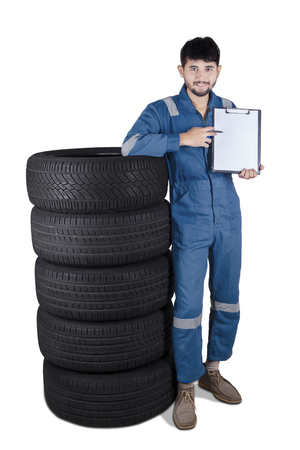 service man: Middle eastern mechanic standing next to a pile of tires while showing empty clipboard, isolated on white background