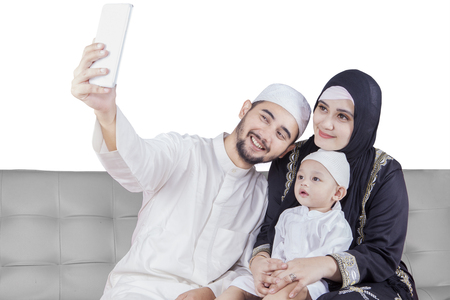 muslim: Happy middle eastern family wearing islamic clothes and taking selfie picture with a smartphone while sitting on the sofa Stock Photo