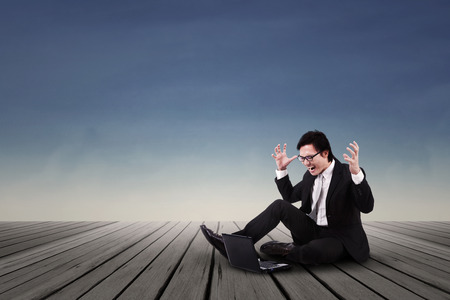 indignant: Asian businessman angry and shouting while sitting on the wooden floor