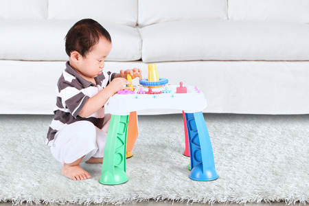 baby toys: Portrait of baby boy playing with colorful toys indoors at home Stock Photo