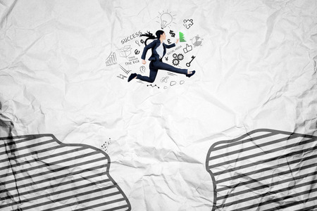 financial cliff: Young female worker jumping through a gap while carrying a document, shot with crumpled background Stock Photo