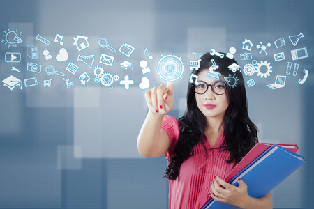 social web: Female college student touching a button with web icons or social media on the futuristic interface