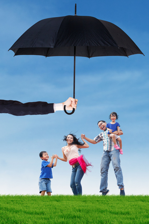 family life: Image of cheerful family enjoy holiday and jumping together at field under umbrella. Life and family insurance concept