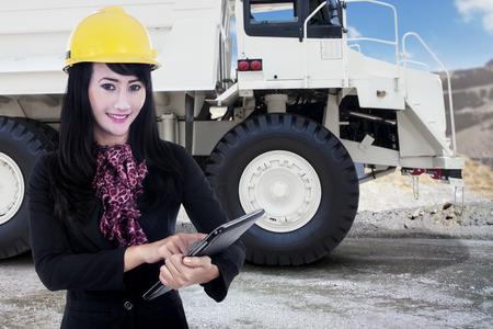 camion minero: Hermoso de negocios la celebraci�n de una tableta digital con un carro de mina en el fondo, tiro en la mina