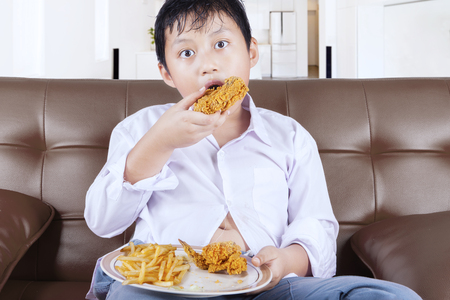 couch potato: Picture of a little boy enjoying fried chicken and french fries while sitting on the sofa at home