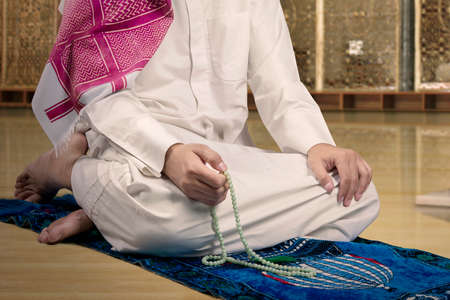 devout: Close up of devout muslim person wearing islamic clothes and using beads to dhikr in the mosque Stock Photo