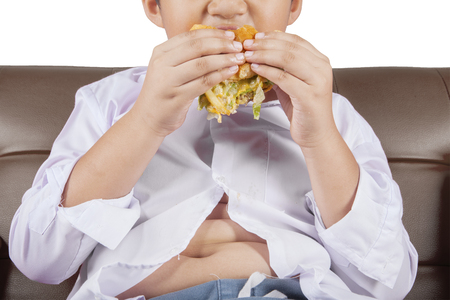 junks: Close up of a little boy with potbelly sitting on the sofa while enjoying a delicious cheeseburger