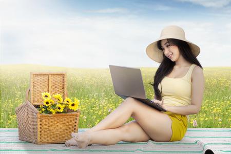 chica sexy: Retrato de la hermosa modelo femenino con un ordenador portátil mientras está sentado en la estera con una cesta en el prado