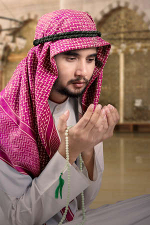 religious clothing: Portrait of Arabic man sitting in the mosque and praying while holding beads and wearing headscarf Stock Photo