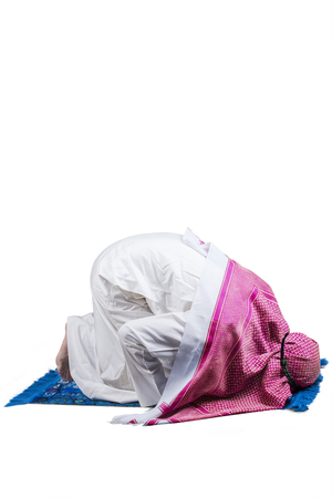 devout: Image of Arabic person wearing islamic clothes and worshiping in the studio with prostration pose