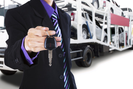 truck driver: Male driver wearing formal suit and gives a car key with the trailer truck background carrying new cars Stock Photo