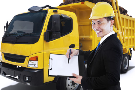 asian business man: Male entrepreneur holding a clipboard while smiling at the camera with a delivery truck carrying palm fruit