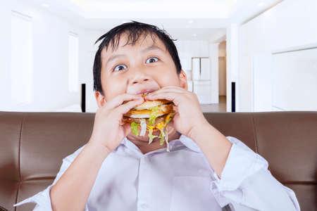 comida chatarra: Imagen de un divertido niño sentado en el sofá mientras come una hamburguesa grande en casa