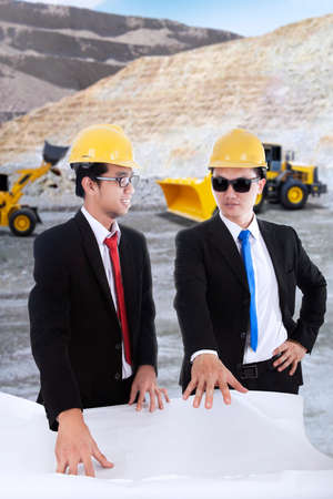 foremen: Portrait of two young foremen discussing at the mining sites while looking at the blueprint