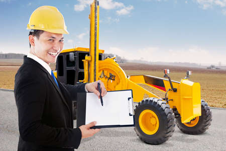 street shot: Male contractor showing empty clipboard with road grader on the street, shot outdoors Stock Photo