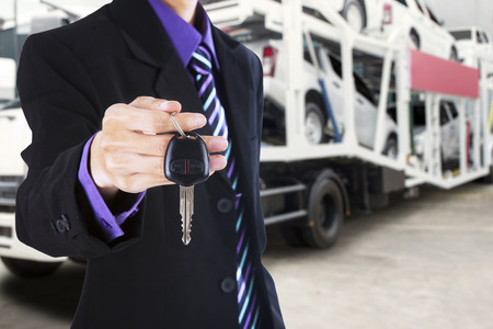 car carrier: Businessman hand giving a car key with a trailer truck carrying new cars on the background