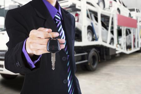 carga: La mano de negocios que da una llave del coche con un camión de remolque que lleva los coches nuevos en el fondo Foto de archivo