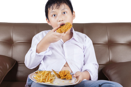 potato fries: Portrait of a little boy sitting on the sofa while eating fried chicken and french fries
