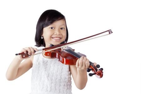 Portrait eines fröhlichen kleinen Mädchens lächelnd in die Kamera beim Spielen einer Violine im Studio