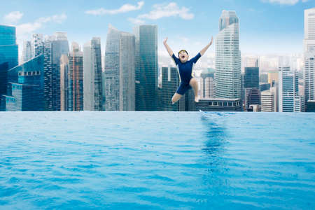 asian boy: Cheerful little boy jumping into the pool while enjoy holiday at the skyscraper rooftop