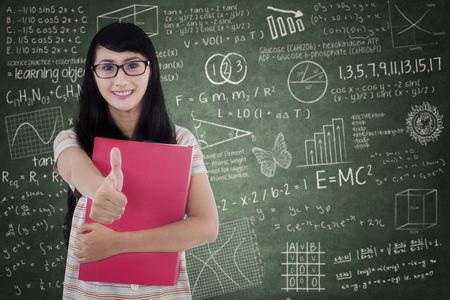 Porträt der weiblichen College-Student zeigt Daumen nach oben, während Ordner halten und in der Klasse stehen Standard-Bild