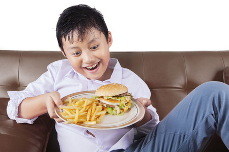 junks: Portrait of hungry boy sitting on the sofa while holding a plate of hamburger and french fries Stock Photo