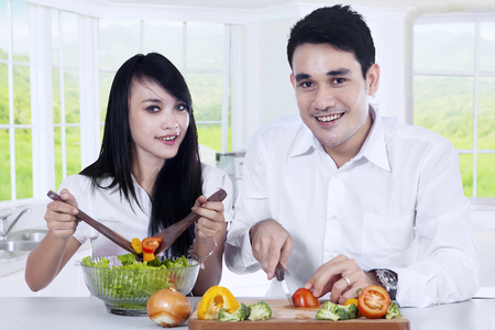 woman eat: Photo of two vegetarian couple smiling on the camera while preparing vegetable salad in the kitchen at home